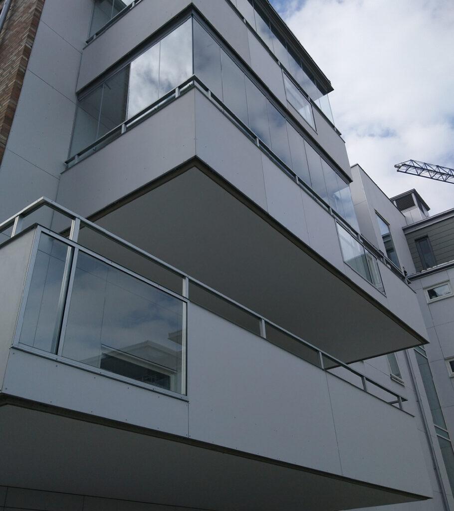 Det är vanligt att räcken med skivbeklädnad används då balkongerna ska vara diskreta och smälta in i fasaden men skivbeklädnaden skapar även stora möjligheter att ge byggnaden extra färgklickar!